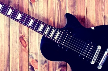 electric-guitar-on-a-wooden-table_1204-146